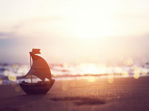 Игрушка маленькой лодки силуэта на песке на пляже захода солнца.