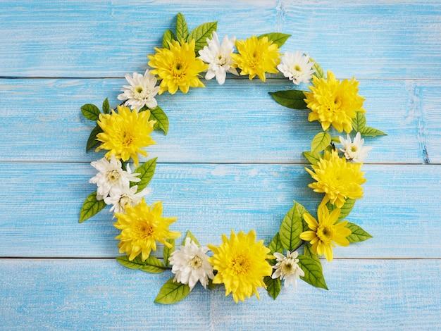 Закройте вверх по белым и желтым цветкам хризантемы в форме круга на голубой древесине.