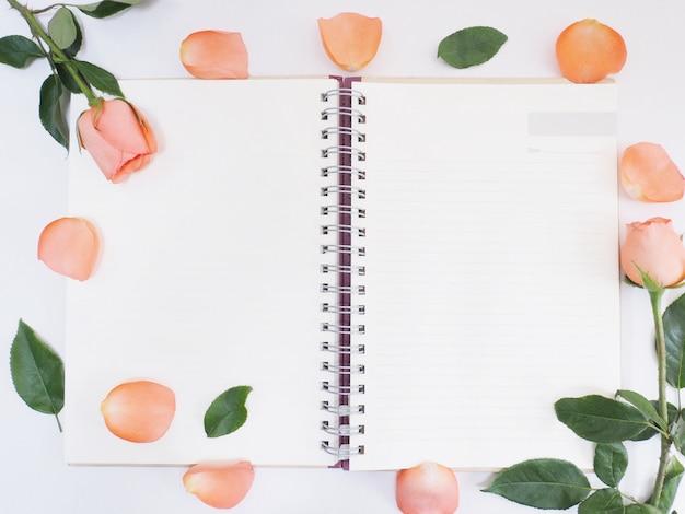 Роза с зелеными листьями на блокноте