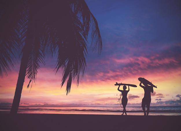 サンセットビーチでサーフボードを運ぶサーファーの人々のシルエット