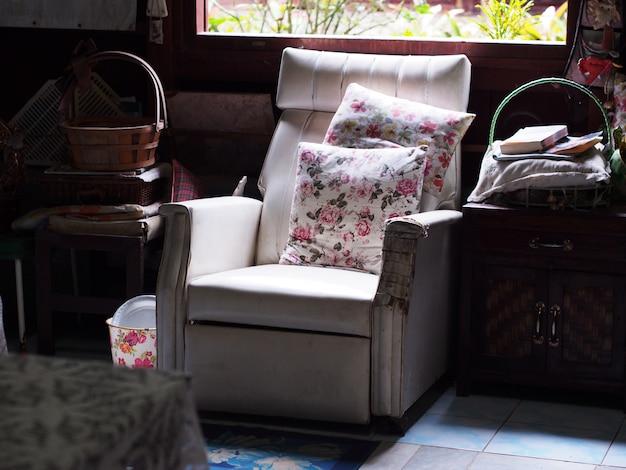 乱雑なリビングルームの窓の近くのヴィンテージの白い古いソファ
