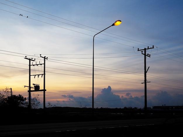 日の出の空を背景に電柱とケーブルのシルエット。エネルギーと技術。
