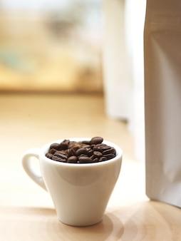 白いカップでコーヒー豆の焙煎を閉じる