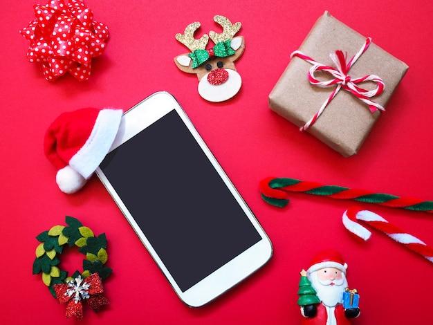再背景にサンタクロースの帽子とクリスマスの飾りと携帯電話を閉じます。