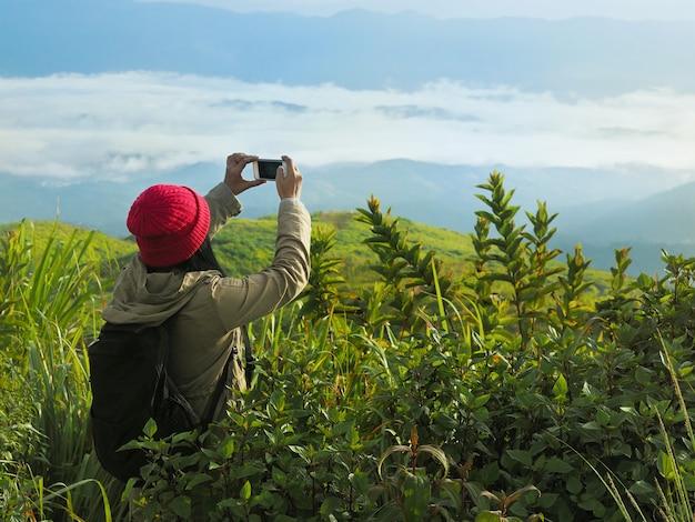 赤い帽子の女性観光バックパッカーが山でスマートフォンで写真を撮る