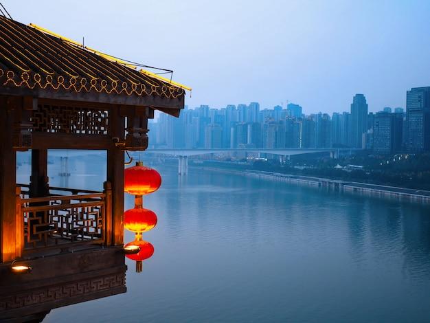 中国の重慶の水の近くにあるダウンタウンの古い建物と近代的な建物を風景します。