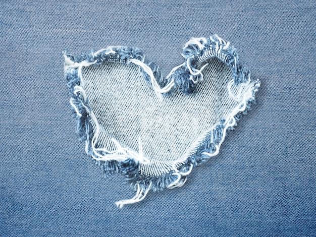 Форма сердца разорвал джинсовую джинсовую текстуру