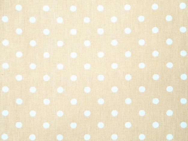 白い水玉模様の背景を持つ表面のクリーム色の綿生地を閉じます。