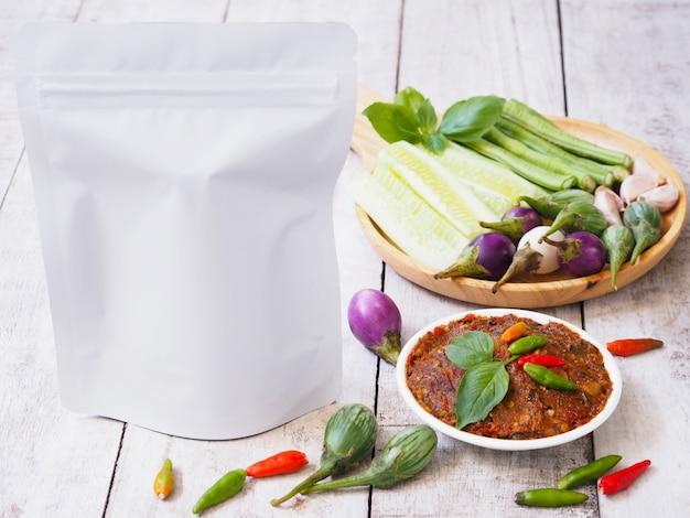 スパイシーな発酵魚の唐辛子ペーストのディッピングと白いヴィンテージの木製のテーブルに新鮮な熱帯野菜を詰めた白い空白のジッパーバッグ。