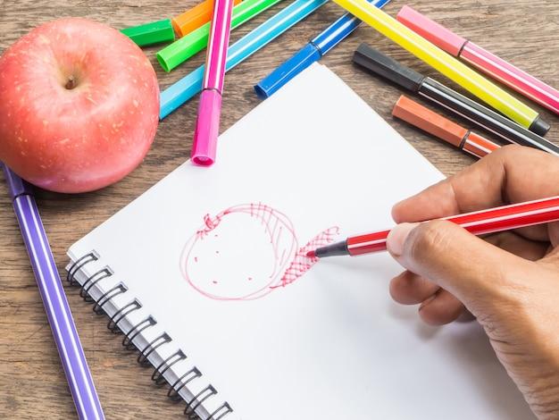 赤いリンゴを描く手のペンを手に