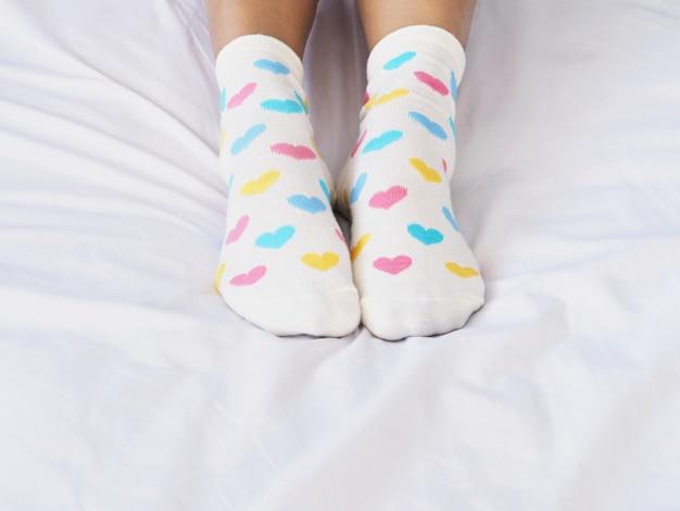 パステル調のハート形のパターンを持つ白い靴下を着ている女性の足