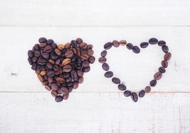 木製の背景にハートの形のコーヒー豆。
