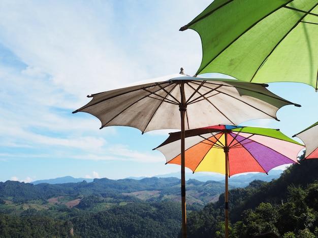 Закройте красочные зонтики на горы и голубое небо.