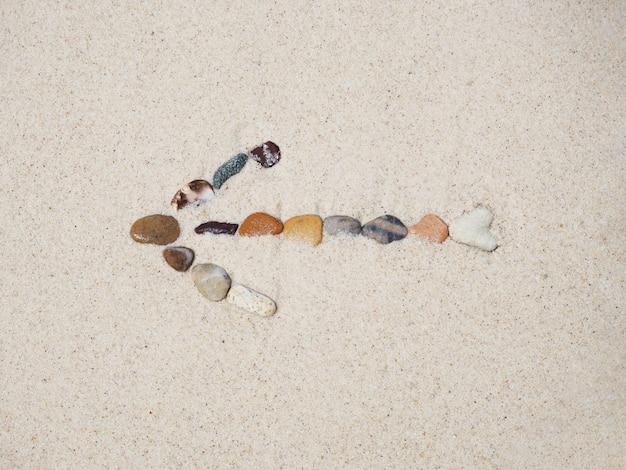 Знак стрелки камней на песке пляжа.
