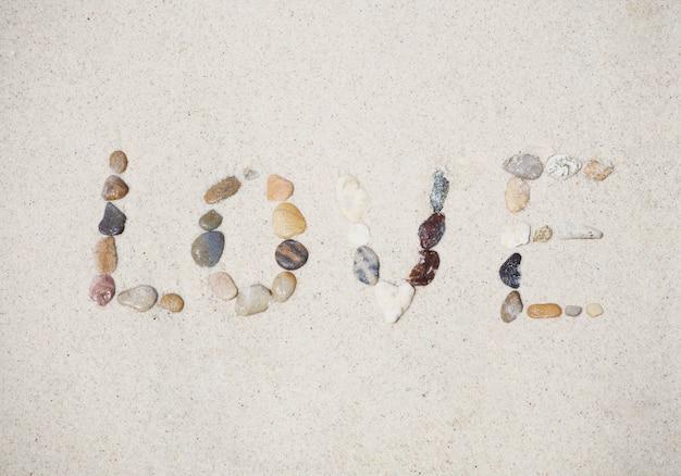 砂の夏のビーチに小石で作られた愛のメッセージ