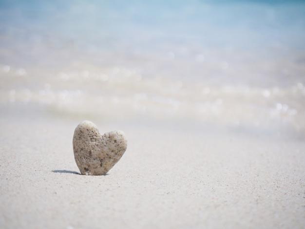 石のハート形の夏のビーチの砂の上に立って