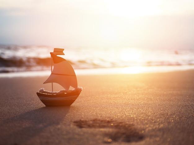 サンセットビーチで砂の上のシルエットの小さなボートのおもちゃ。