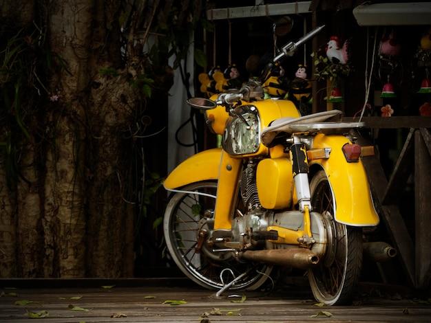 古い黄色のオートバイは、ショーのために保留古代保存の概念