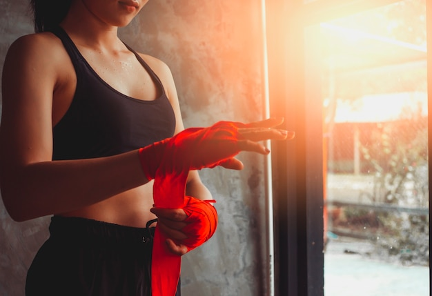 女性の手のクローズアップは赤い包帯を拳します。