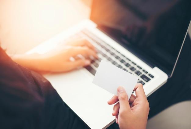 ラップトップコンピュータでチケットを注文するためにクレジットカードを使用しているビジネスマン