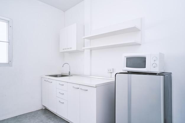 Белая чистая кухонная комната со встроенной мебелью