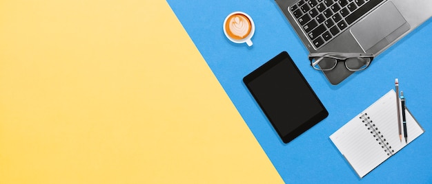 ラップトップ、ノートブック、タブレット、コピースペース付きのホットコーヒーと近代的なオフィスのデスクトップ職場