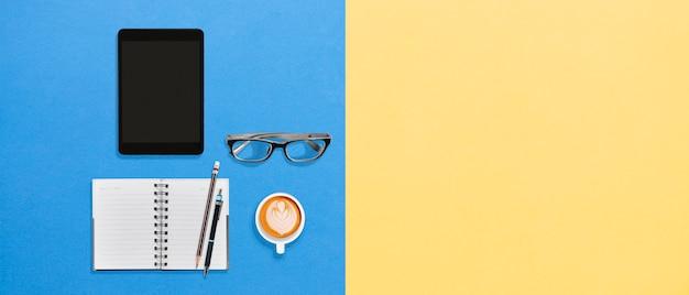 タブレットとコピースペースを持つホットコーヒー泡立つ飲み物と近代的なオフィスのデスクトップ作業スペース