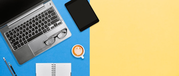 コピースペースとカラフルな背景にラップトップ、タブレット、コーヒーと作業スペースオフィスデスクトップ
