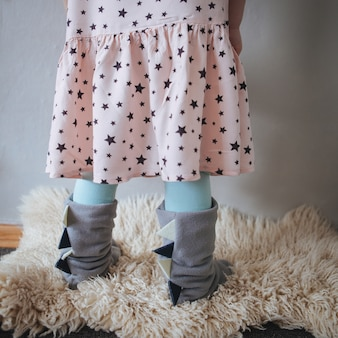 青い家のスリッパで壁に小さな女の子の足