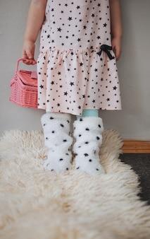 かわいいピンクのドレスで、ピンクのバックセットを持つ女の子