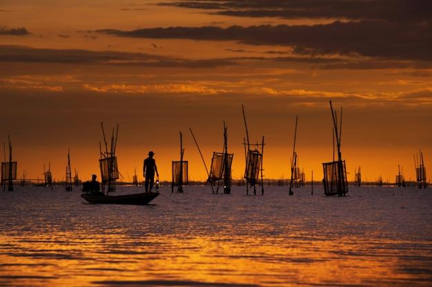 夕日と魚を捕る船の漁師