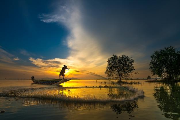 日の出と魚を捕る船の漁師