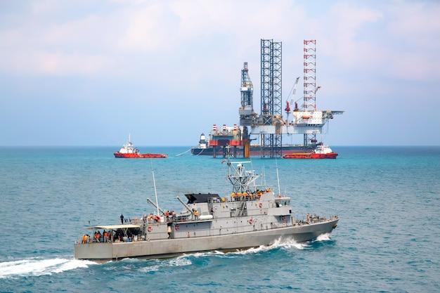 油田掘削プラットフォームの背景とタイの湾のパトロール船
