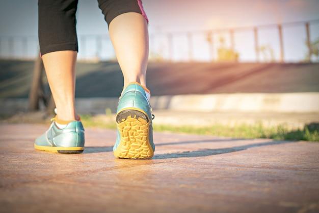 トラック上のフィットネス女性ランナーの足は、スポーツの靴に焦点を当てます。フィットネスとトレーニングウェルネスのコンセプト。