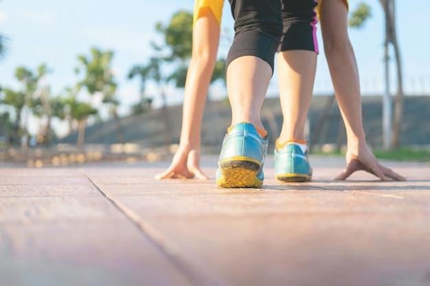 通りで女性のランニングスタートポーズ。女性フィットネス日の出ジョギングトレーニングウェルネスコンセプト。