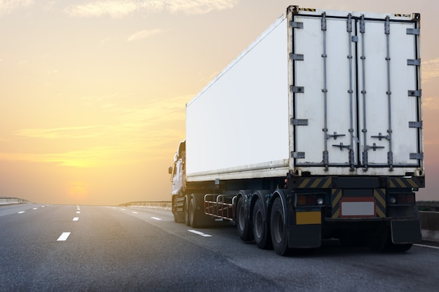 白いコンテナと高速道路上のトラック