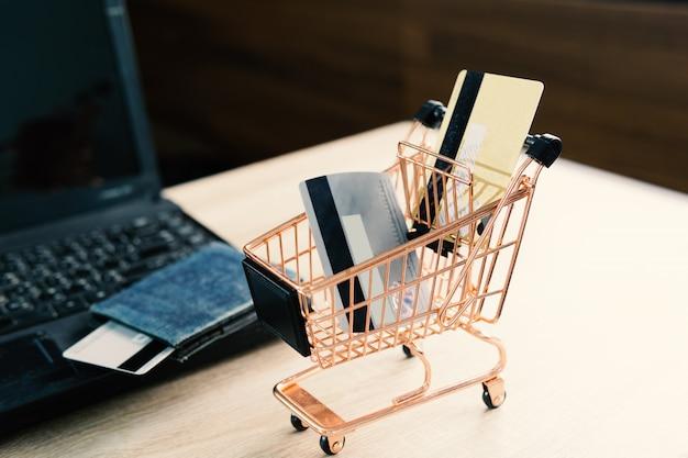 クレジットカードと木製テーブル上のラップトップを使用しています。自宅やオフィスのコンセプトでのオンラインショッピングカート