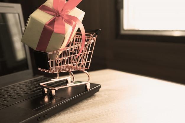 ノートパソコンのキーボードの小さなショッピングカートにギフト用の紙箱赤いリボン。