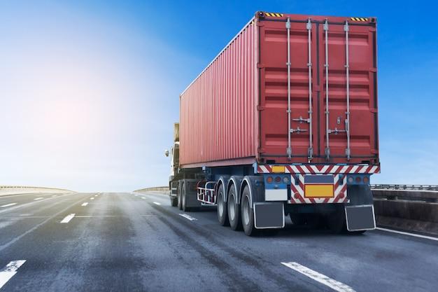 赤いコンテナーと高速道路道路上のトラック。アスファルト高速道路での輸送