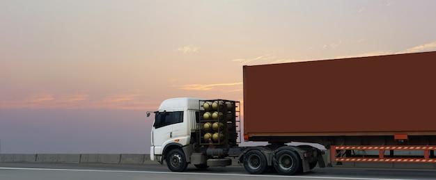 Грузовик на шоссе дорога с красным контейнером, логистический промышленный транспорт наземный транспорт