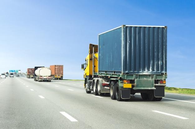 青いコンテナーと高速道路道路上のトラック