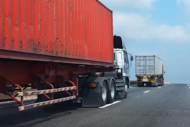 赤いコンテナーと高速道路道路上のトラック、空を背景にアスファルト高速道路上の輸送