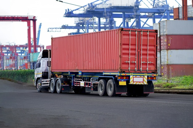 港湾ビジネスの赤いコンテナトラック物流。輸送業界の輸送産業。輸入、輸出物流産業