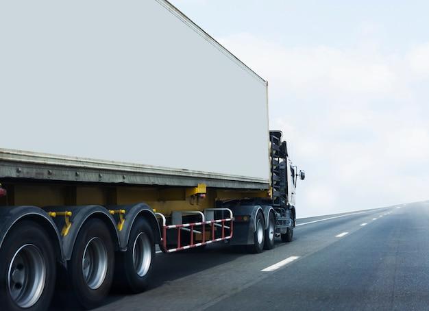 Белый грузовик на шоссе с контейнером.