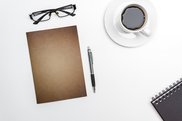 Вид сверху пустой блокнот, ручка и очки на белом фоне стола.