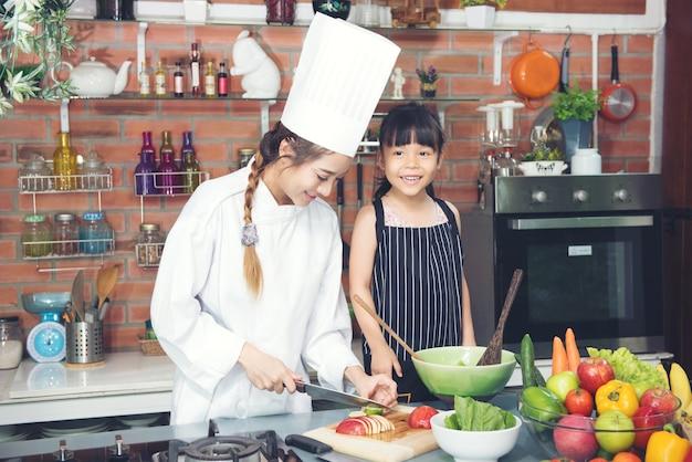 キッチンルームで笑っている子供の女の子と女性のシェフ