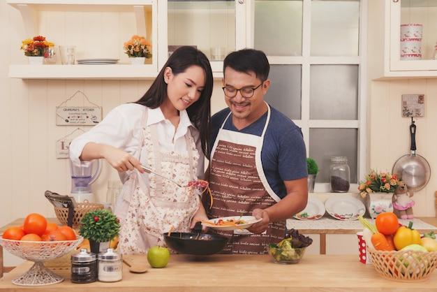 家庭のロフトキッチンで健康的な料理を料理している幸せなアジアのカップル