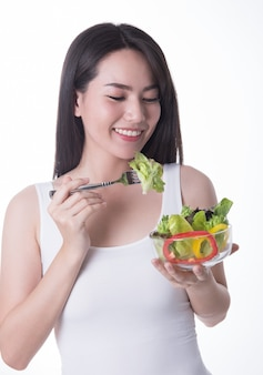 白い背景で隔離のサラダと健康的なアジアの女性