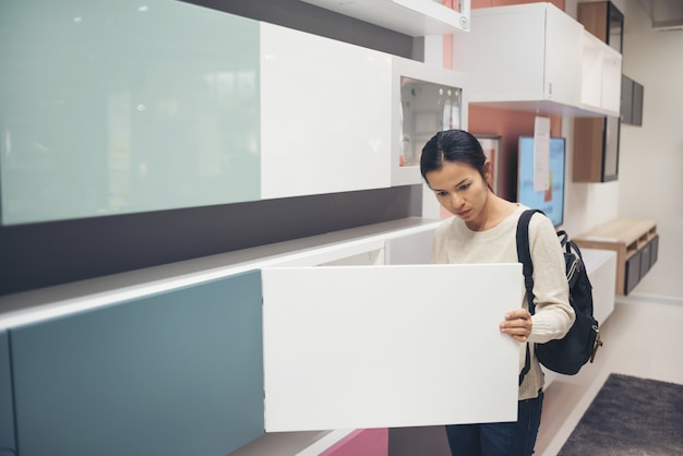 アジアの若い女性がモダンな家庭用家具店で家具を選ぶ