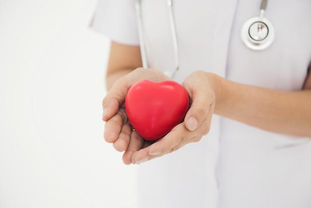 看護師は手を使用して心臓の形の概念を示す